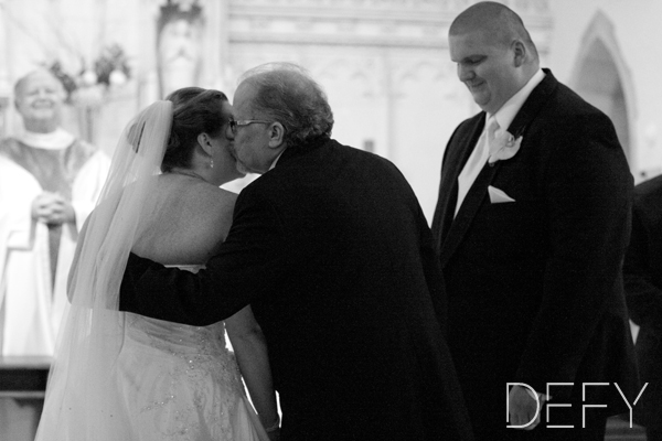 Father giving bride kiss