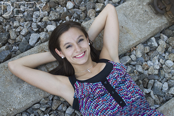 senior girl laying on train tracks
